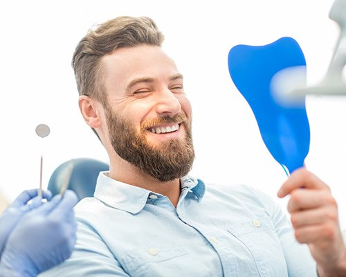 Man looking in mirror smiles at his dental bridges in Center