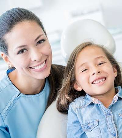 Smiling child and dentla team member in exam room