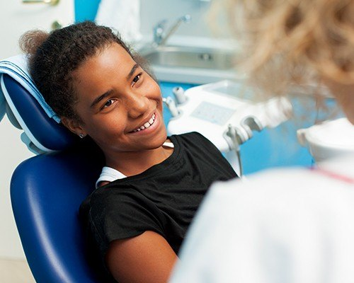Adolescent girl smiling in dental chair