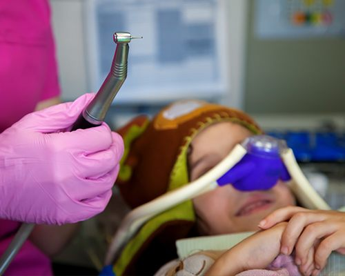 Child in dental chair with nitrous oxide mask