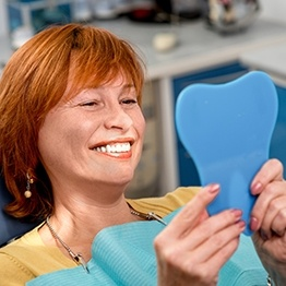 Older woman in dental chair looking at her smile