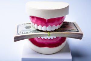 model of a mouth biting down on money