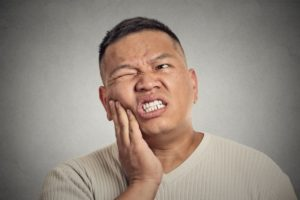 Pained man with hand on cheek needs to visit emergency dentist center