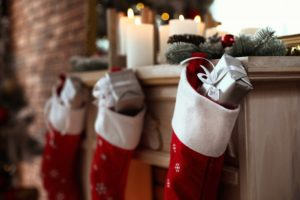 red stockings on the mantle with silver gifts inside of them