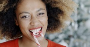 woman biting into a candy cane